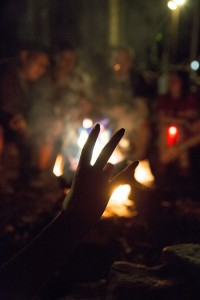 hand making the Sparky pitchfork ASU gesture backlit by a campfire surrounded by campers