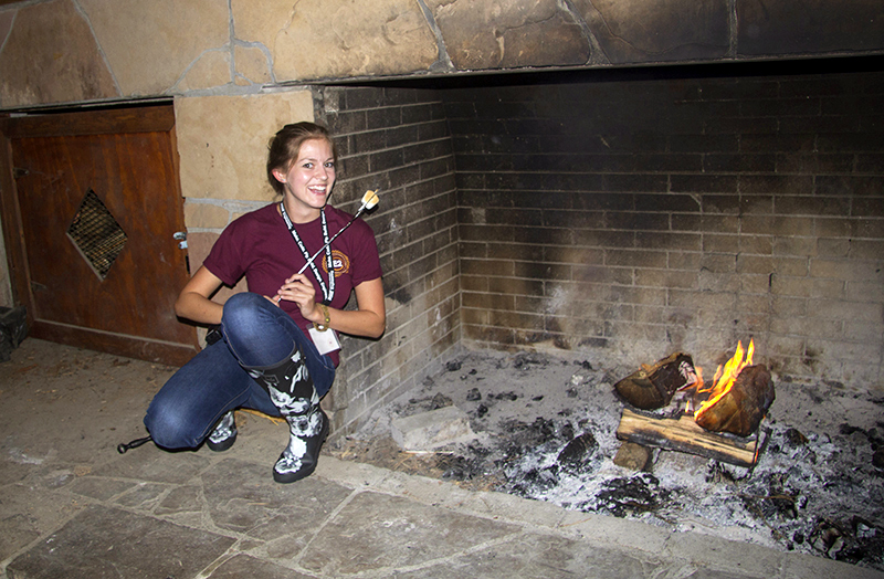 A young woman roasts a marshmallow in a large, rustic fireplace.