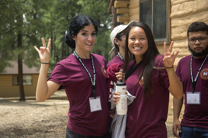 Two young women smile for the camera and display the ASU pitchfork gesture