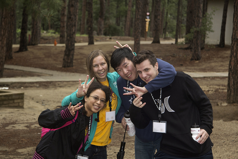A group of 4 students, arms around one another, smile and lean in for a photo while making the ASU pitchfork gesture.